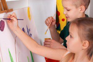 Children painting finger on easel. Group of kids with teacher.
